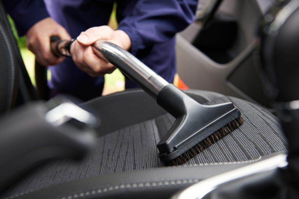 Sitzpolster im Auto werden mit einem Staubsauger gereinigt