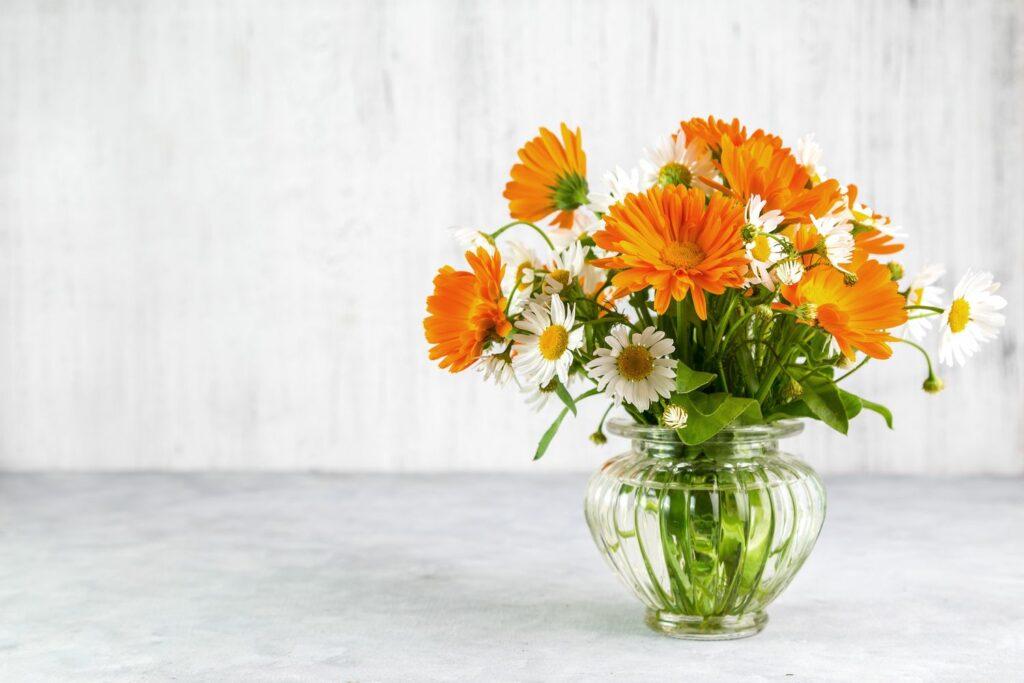 Vase mit Ringelblumen und Gänseblümchen